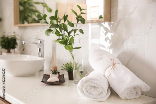 Fototapeta Towels and green plants on white countertop in bathroom. Interior design obraz