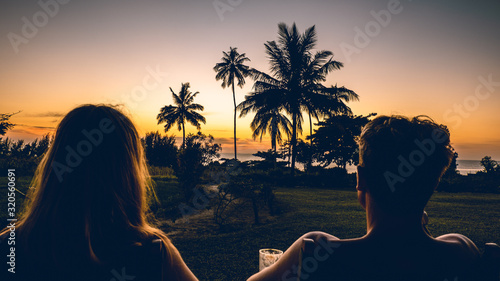 Obraz a couple man and a woman watching the sunset with palmtrees in Tanzania Africa - fototapety do salonu