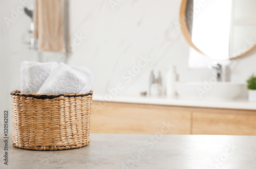Fototapeta Rolled fresh towels on grey table in bathroom. Space for text obraz