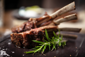 Grilled lamb chops served with a branch of rosemary