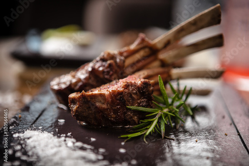 Photo Grilled lamb chops served with a branch of rosemary