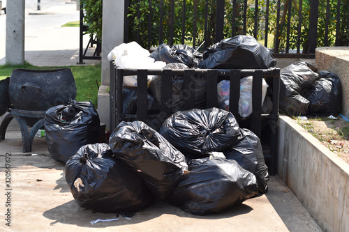 Fototapety, obrazy: Pile of black garbage on the footpath at side road in big city, pollution trash