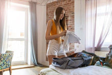 Young Woman Packing Backpack I...