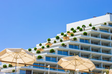 Resort Hotel Terrace Exterior Building With Umbrella In Yard Sunny Day Summer Time Vacation Season Destination Site On Red Sea Waterfront Area Blue Sky Background