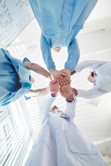 Group of pulmonology department medical workers stacking hands before starting long day of work
