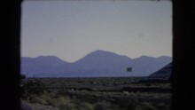 LAS VEGAS NEVADA-1966: Driving Down Road In Rural Landscape Past Texaco Sign And A Road Sign To Jean Goodsprings 1 Mile