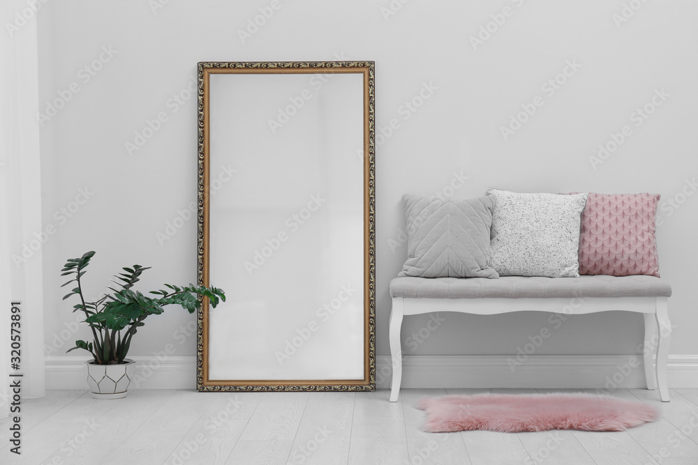 Fototapeta Modern large mirror and comfortable bench near light wall in room