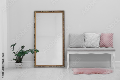 Fototapeta Modern large mirror and comfortable bench near light wall in room obraz