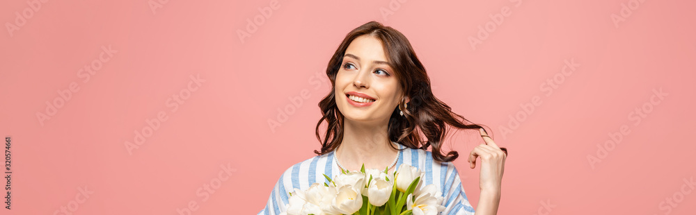 Fototapeta panoramic shot of cheerful girl touching hair while holding bouquet of white tulips isolated on pink