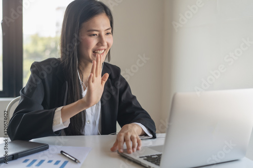 Photo Happy young asian business woman waving hands to greeting partner during making video conference with her team