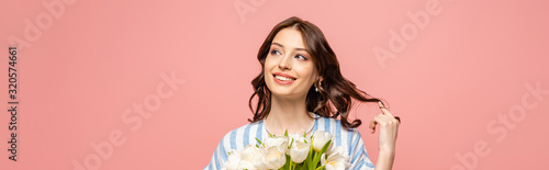Fototapeta panoramic shot of cheerful girl touching hair while holding bouquet of white tulips isolated on pink obraz