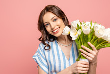 Happy Girl Smiling At Camera While Holding Bouquet Of White Tulips Isolated On Pink