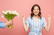 cropped view of man presenting bouquet of white tulips to excited young woman showing winner gesture isolated on pink