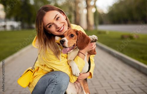 Stampa su Tela Happy woman hugging dog in park