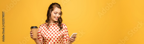 panoramic shot of happy young woman holding coffee to go and using smartphone is Fototapet