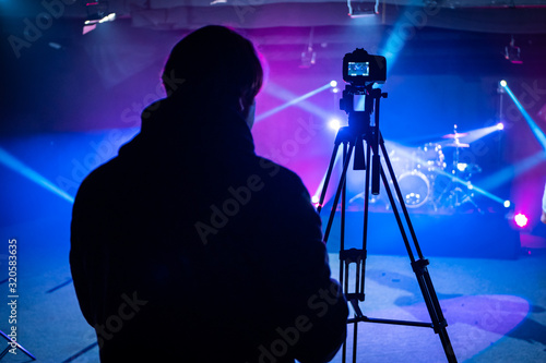 Camera Man or Director operating a Video Camera or DSLR Shooting a music video or concert with stage lighting Canvas Print