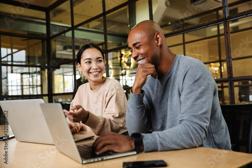Image of multiethnic young coworkers working on laptops in office - fototapety na wymiar