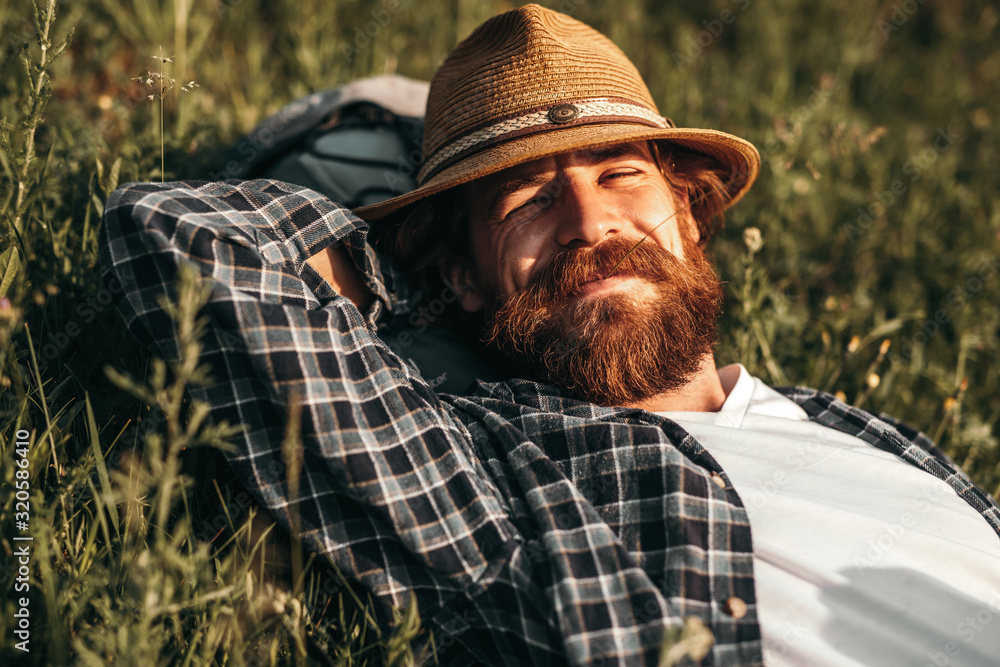 Fototapeta Bearded traveler chewing straw white resting on grass