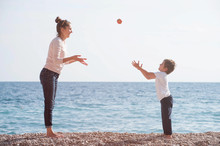 Active Mother Female And Happy Small Kid Playing Leisure Games On Sea Beach Throwing Apple In Air In Spring