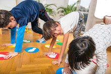 Group Of Children Playing Twister Indoors