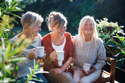 Fototapeta Senior women friends with coffee sitting outdoors on terrace, resting. obraz