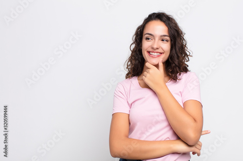 Fototapety, obrazy: young pretty woman smiling with a happy, confident expression with hand on chin, wondering and looking to the side against white wall