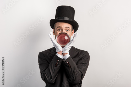 Photo professional magician holding magic ball, isolated on grey