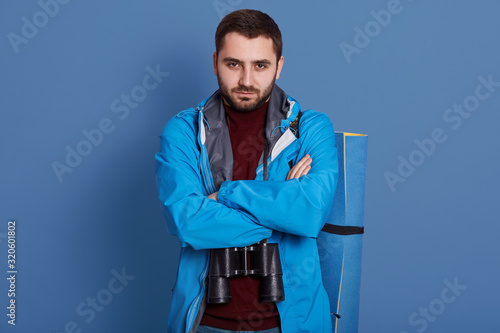 Fényképezés Horizontal shot of bearded handsome man standing isolated over blue background with folded hands, traveler with mat and binoculars, wearing jacket, looking at camera, expresses angerand spite