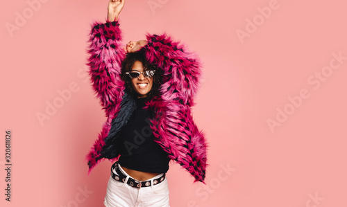 Black woman in a black faux fur jacket, Close up fashion portrait of crazy hipster African girl with funny curly hairstyle and vivid faux fur coat, urban trendy style. Horizontal.copy space