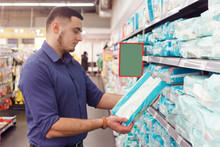 Man With Diaper Pack In Supermarket Reading Product Information