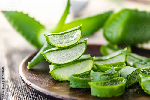 Fotografiet Slices of aloe vera in a bowl on a wooden table.