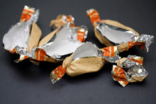 Empty Candy Wrappers Close-up. Packages Of Chocolates On A Black Background. Weight Gain Concept, Living Hard Without Sweets.
