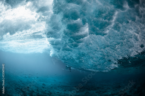 Fotografiet Underwater view of the surfer passing the ocean wave
