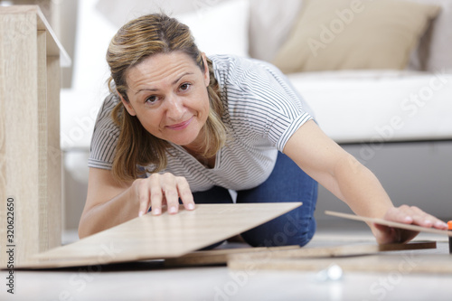 Fototapeta happy smiling woman assembling wood furniture obraz