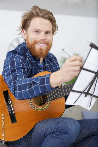 Fototapeta attractive bearded man learning a song obraz