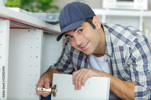 Fototapeta professional handyman installing cabinet door in the kitchen obraz