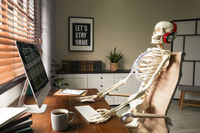 Human Skeleton With Headphones Using Computer At Workplace