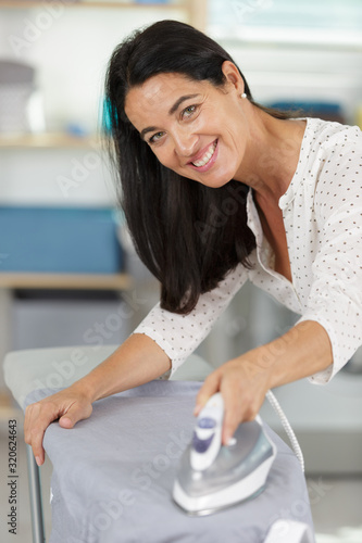 Fototapeta a happy woman ironing clothes obraz