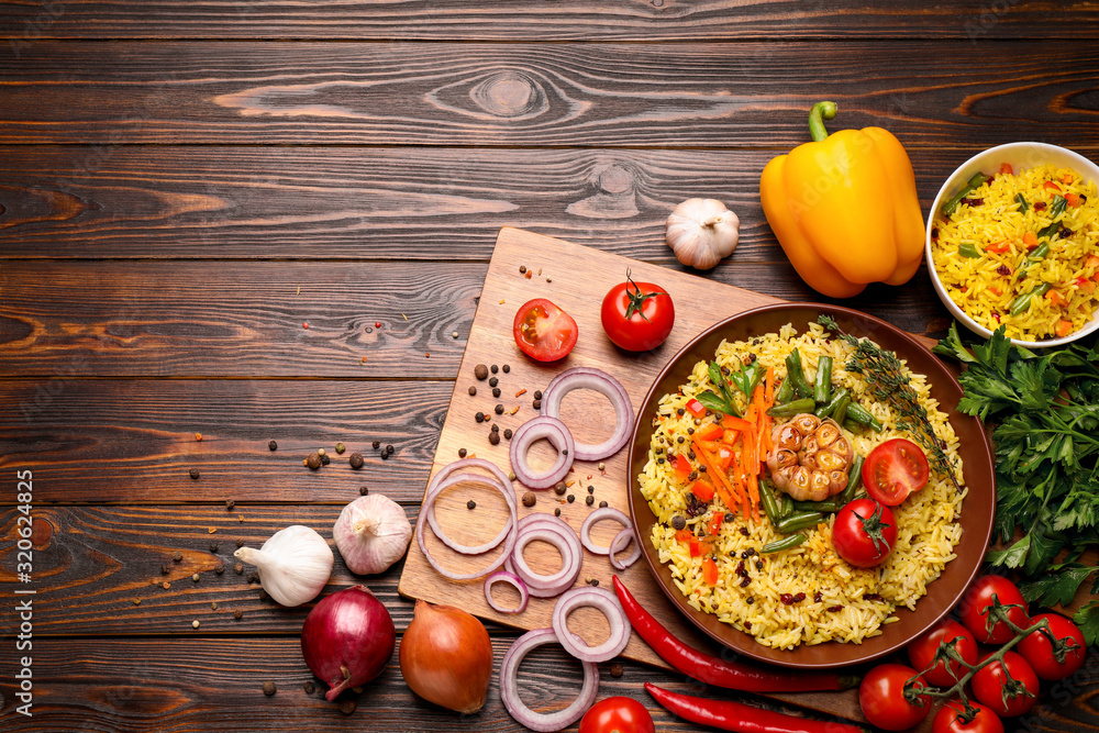 Fototapeta Flat lay composition with tasty rice pilaf on wooden table. Space for text