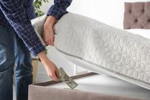 Man Hiding Dollar Banknotes Under Mattress In Bedroom, Closeup. Money Savings