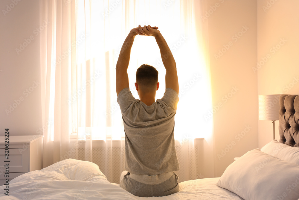 Fototapeta Young man stretching on bed at home, view from back. Lazy morning