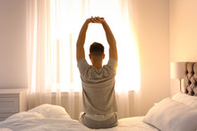 Young Man Stretching On Bed At...