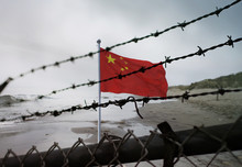 China Border Fence. Chinese Flag Behind A Steel Wire Mesh