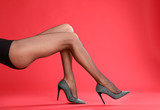Fototapeta Kawa jest smaczna - Woman wearing black tights and stylish shoes on red background, closeup of legs