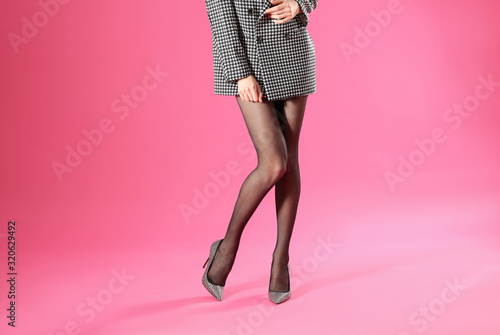 Obraz Woman wearing black tights and stylish shoes on pink background, closeup of legs - fototapety do salonu