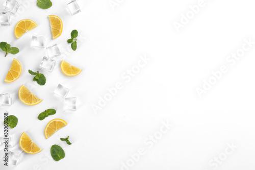 Fototapeta Lemonade layout with lemon slices, mint and ice cubes on white background, top v