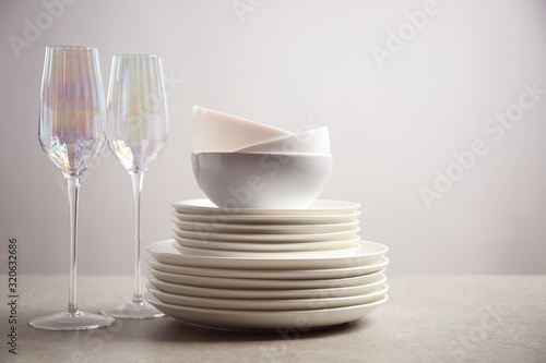 Photo Set of clean dishes and glasses on light grey table