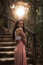 Side View Of Gentle Young In Pink Dress And White Lace Bra Standing In Autumnal Park Looking Over Shoulder In Back Lit