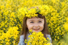 A Little Girl In A Field Of Flowering Yellow Rapeseed. Rapeseed Field. Girl With Yellow Flowers