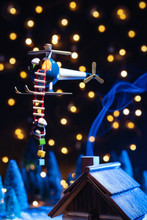 Tiny Santa Claus Climbing Down From Ladder Of Toy Helicopter Above Tint House On Winter Night With Lights On Blurred Background